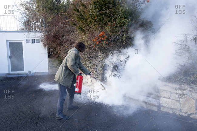 Man extinguishing cable fire in garden near the house