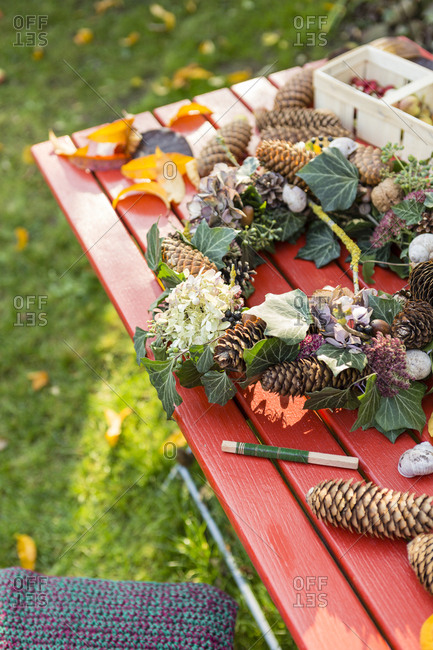 Autumnal wreath with hortensia- pine cones and ivy on garden table