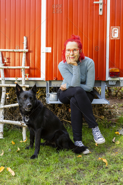 Portrait of content senior woman with red dyed hair sitting in front of red trailer in the garden with her dog