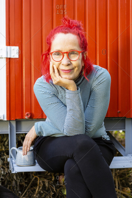 Portrait of content senior woman with red dyed hair sitting in front of red trailer in the garden
