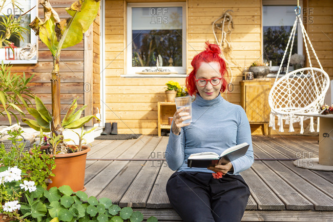 Portrait of smiling senior woman with red dyed hair sitting on terrace in front of her house reading a book