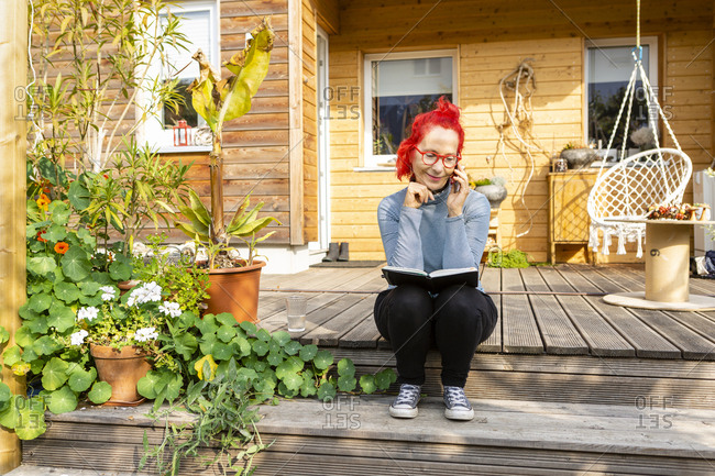 Smiling senior woman with red dyed hair on the phone sitting on terrace in front of her house reading a book