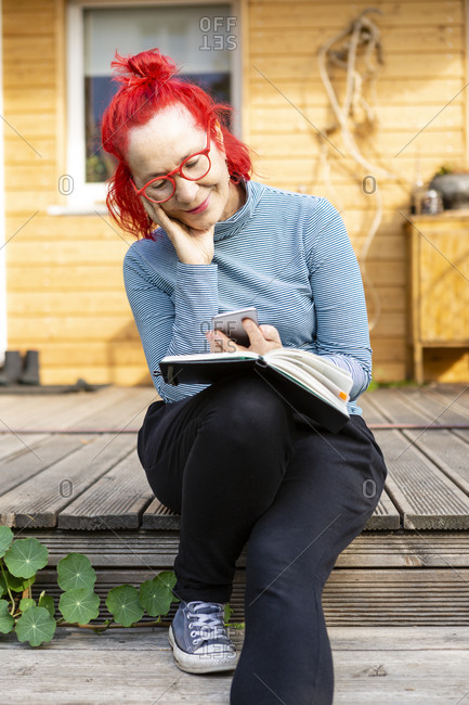 Portrait of smiling senior woman with red dyed hair sitting on terrace in front of her house using cell phone