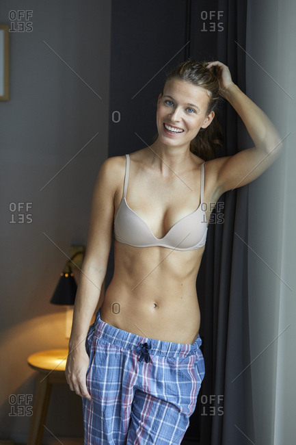 Portrait of laughing young woman standing wearing bra and pyjama pants