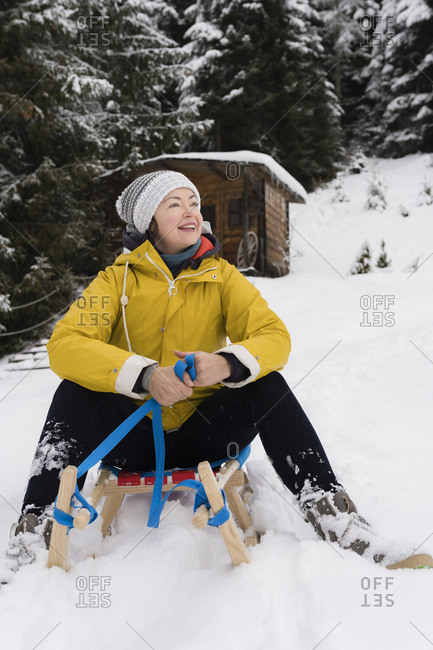 Austria- Tyrol- Thurn- content mature  woman sitting on sledge in the snow looking at distance