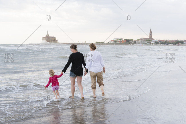 Italy- Caorle- two women walking with girl at the waterfront