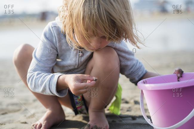 Little girl with bucket on the beach