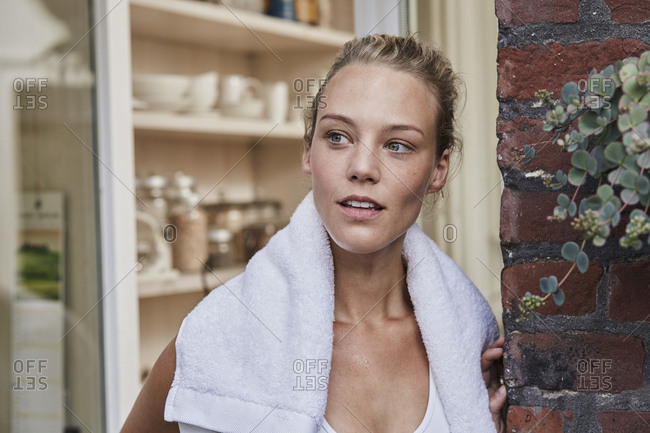 Portrait of sporty young woman with towel around her neck at house entrance