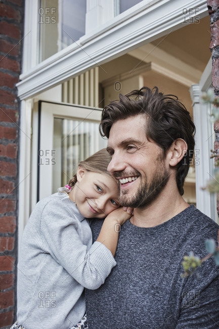 Smiling father with daughter at house entrance of their home