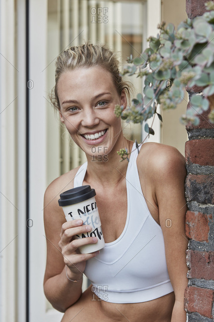 Portrait of smiling sporty young woman with takeaway drink at house entrance