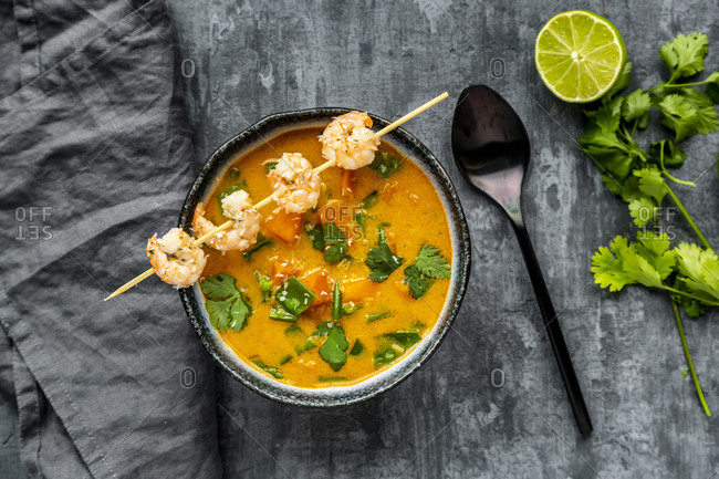 Bowl of sweet potato soup with  shrimps- coconut flakes and fresh coriander