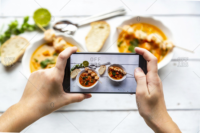 Girl taking photo of bowls with sweet potato soup with smartphone- close-up