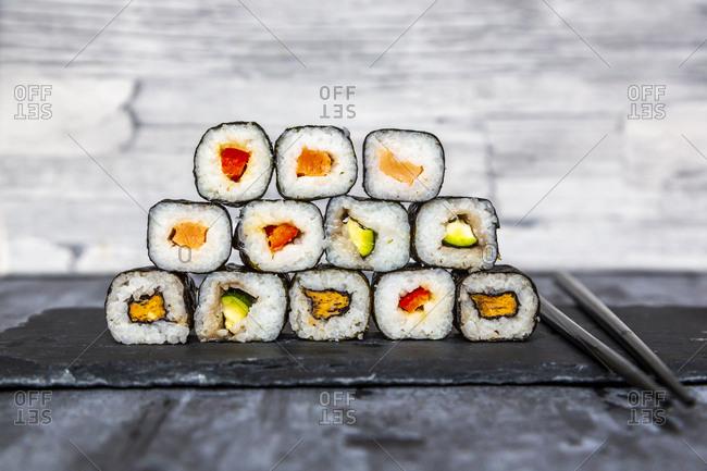 Stacked sushi on slate slab- chop sticks