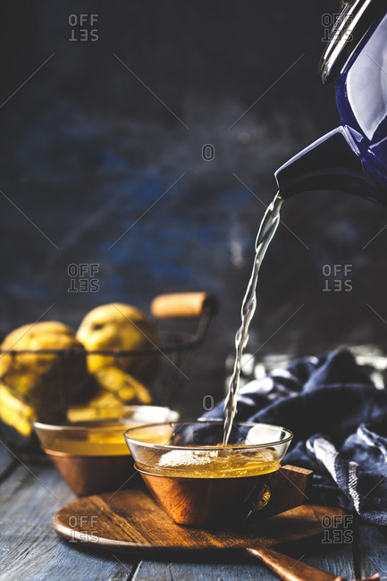 Pouring homemade hot quince infusion into tea cup