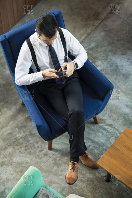 Top view of businessman sitting in blue armchair using smartphone