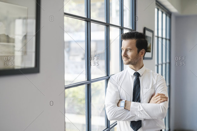 Confident businessman standing in office looking out of window