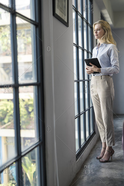 Confident businesswoman with tablet standing in office looking out of window