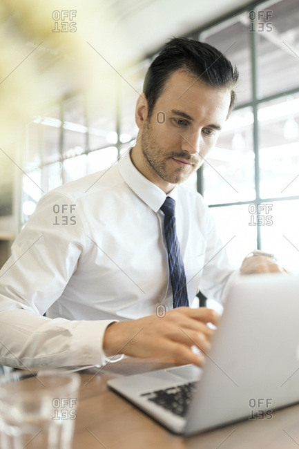 Young businessman working on laptop in cafe on wooden table