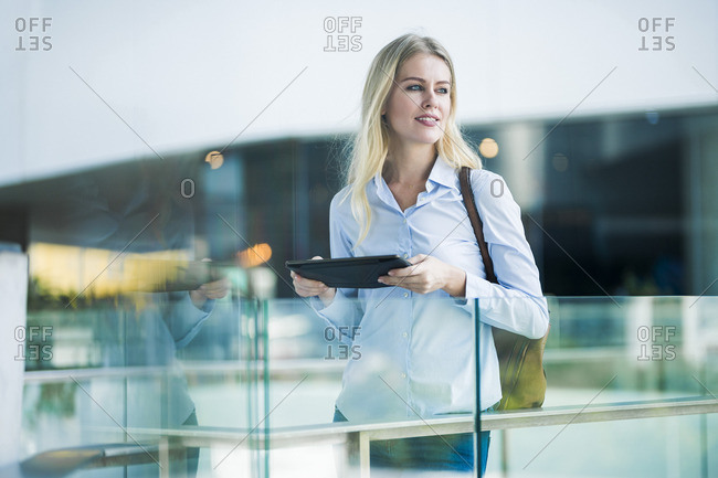 Blond woman with tablet standing at glass railing in the city