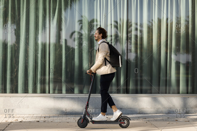 Man with backpack using E-Scooter in the city