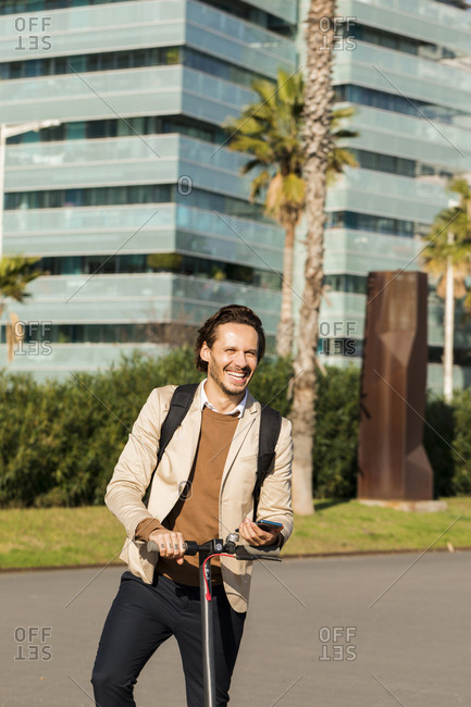 Portrait of laughing man with backpack and E-Scooter in the city