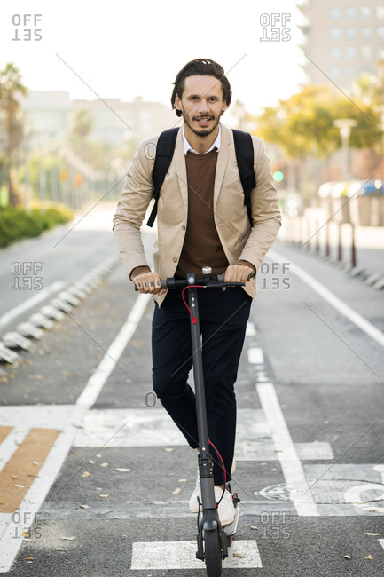 Portrait of man using E-Scooter in the city