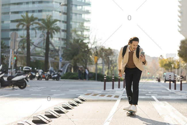 Man looking at cell phone while skateboarding in the city