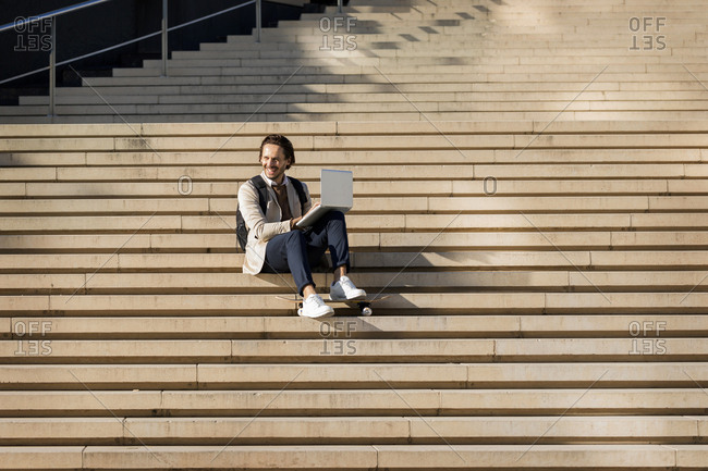 Laughing man with backpack and skateboard sitting on stairs using laptop