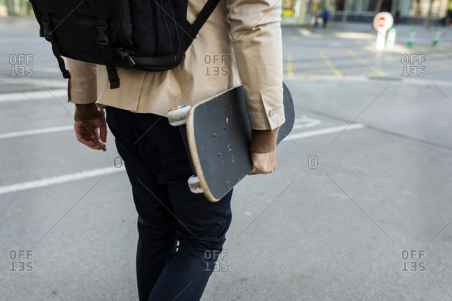 Man with backpack and skateboard in the city- partial view