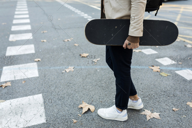 Man with backpack and skateboard crossing the street in autumn- partial view