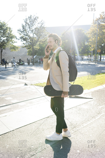 Man on the phone with backpack and skateboard in the city