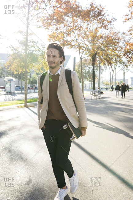 Portrait of man with backpack and skateboard in the city in autumn