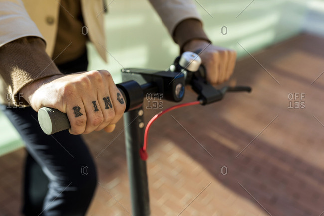 Hand of tattooed man holding handlebar of E-Scooter- close-up