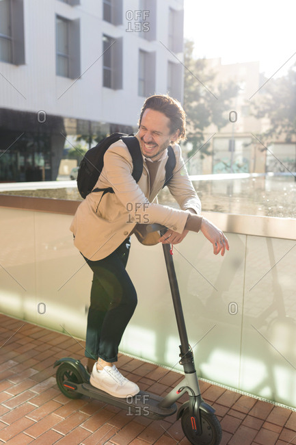 Laughing man with backpack and E-Scooter in the city