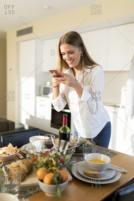 Woman taking pictures of the laid table for a lunch with friends
