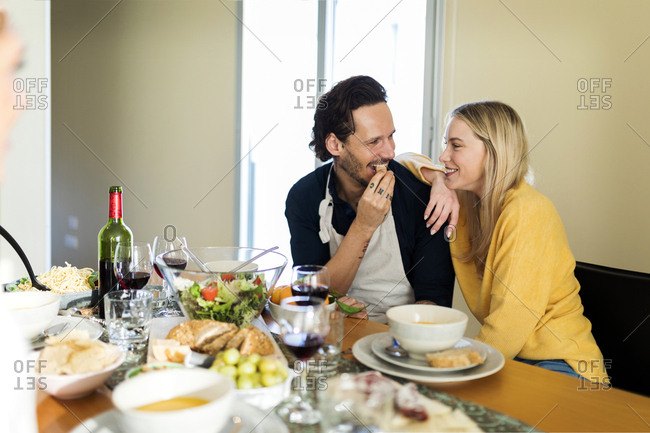 Friends having fun- eating lunch together- couple flirting at the table