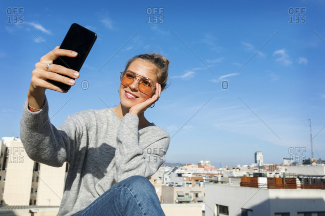 Young woman taking smartphone selfies on an urban rooftop terrace