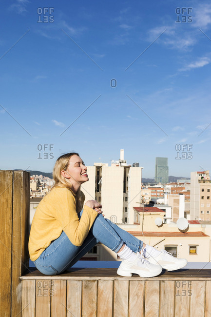 Young woman relaxing on an urban rooftop terrace