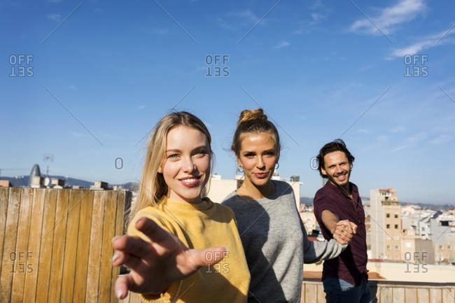 Friends having fun on an urban rooftop terrace- holding hands