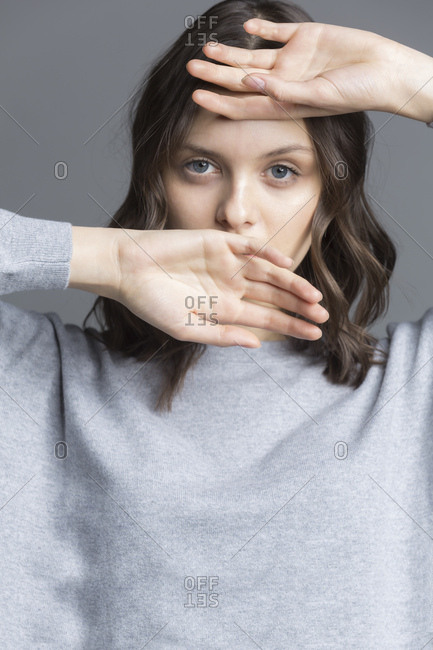 Portrait of brunette young woman- hands over her face