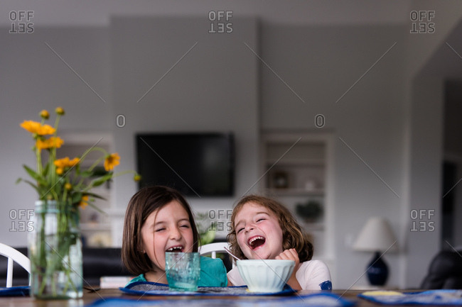 Two little girls laughing over breakfast
