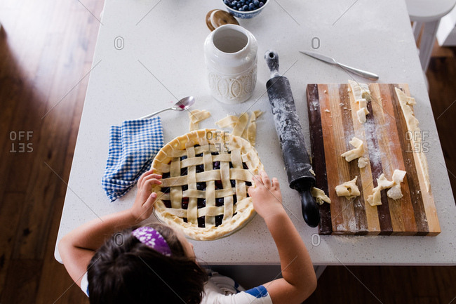 Overhead view of girl making blueberry pie
