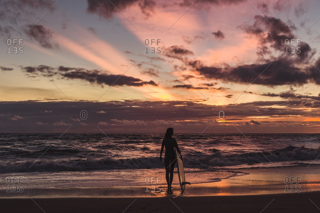 Woman with surfboard walking at beach during sunset