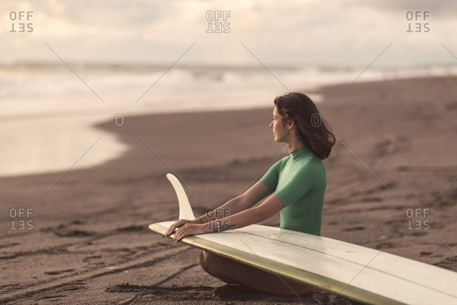 Woman with surfboard sitting at beach during sunset