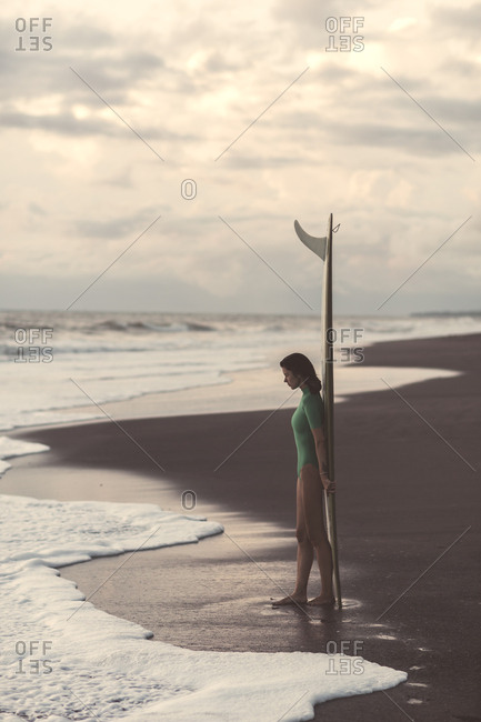 Young woman carrying surfboard at the sea
