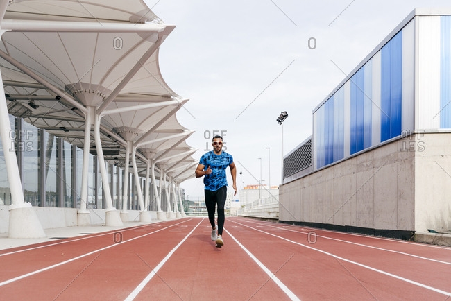Handsome ethnic man with sports wear and sunglasses running on the running track