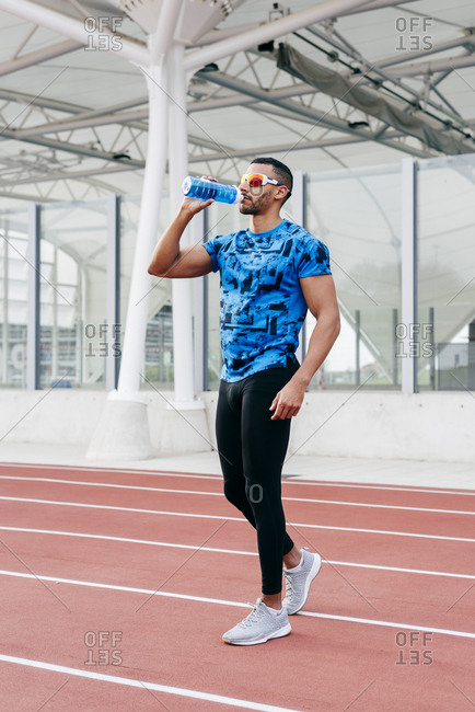 Handsome ethnic man with sports clothes and sunglasses standing and drinking water on the running track