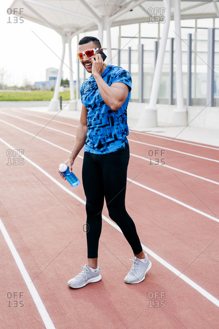 Handsome ethnic man with sports clothes and sunglasses using the phone on the running track