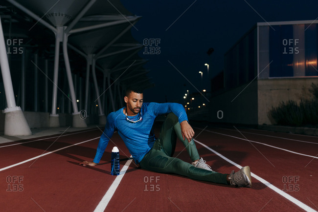 Handsome young african athlete sitting and resting on the floor of the running track