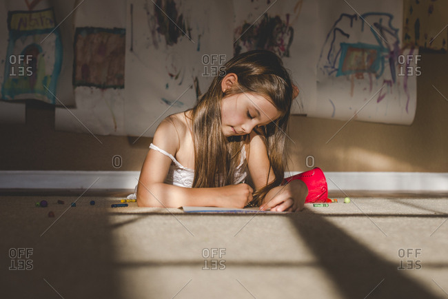Little girl drawing a picture with crayons while on the floor